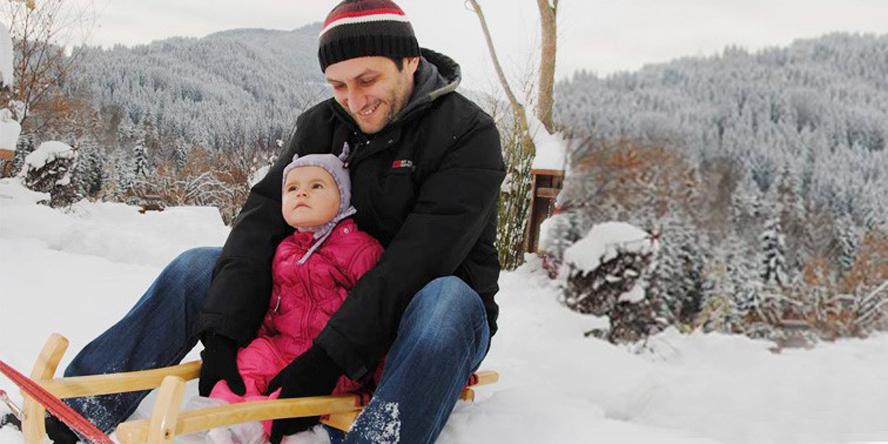 Jürgen Zechner mit gestreifter Strickkappe und schwarzer Winterjacke und seine entzückende kleine Tochter im pinken Skioverall und mit rosa Haube auf einer Rodel im Schnee. Im Hintergrund verschneiter Wald.