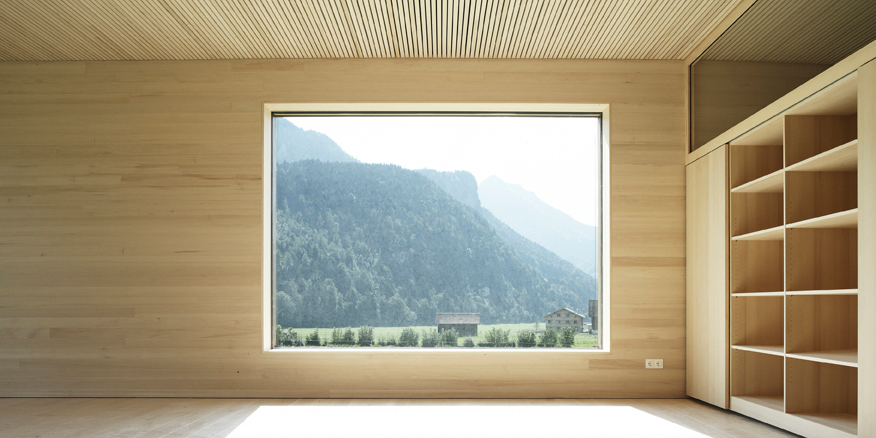 Ein Zimmer aus Holz. In der Mitte ist ein gläsernes Fenster, durch das man die Natur sieht. Auf der rechten Bildseite ist ein Kasten.