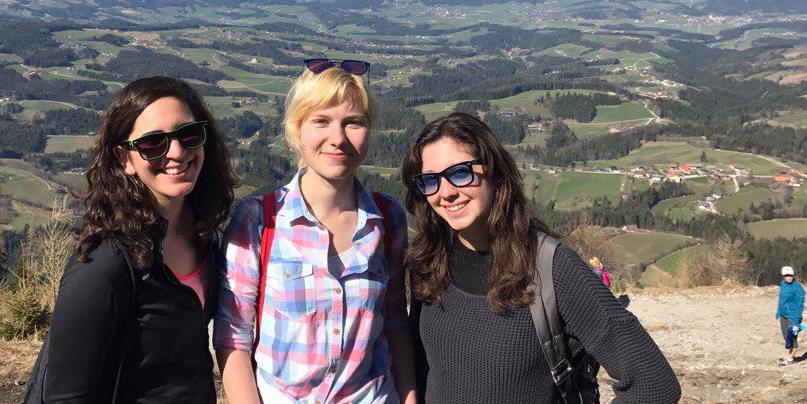 Drei junge Frauen stehen am Gipfel eines Berges und lächeln in die Kamera. Im Hintergrund ist eine weitläufige Landschaft zu sehen.