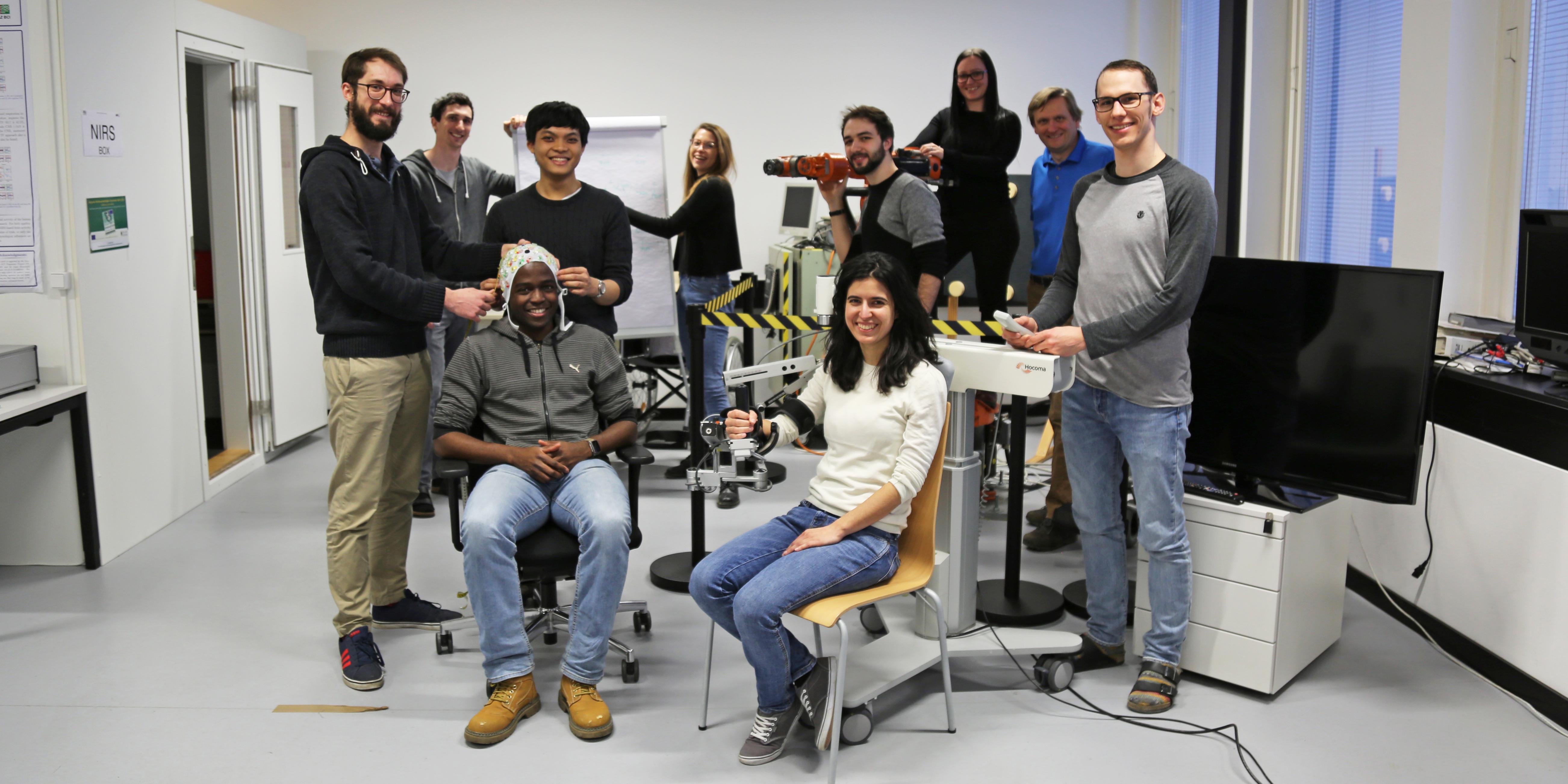 Mitglieder des BCI Racing Teams 2018 mit diversen technischen Assistenzsystemen in einem hell eingerichteten Arbeitsraum am Institut für Neurotechnologie.