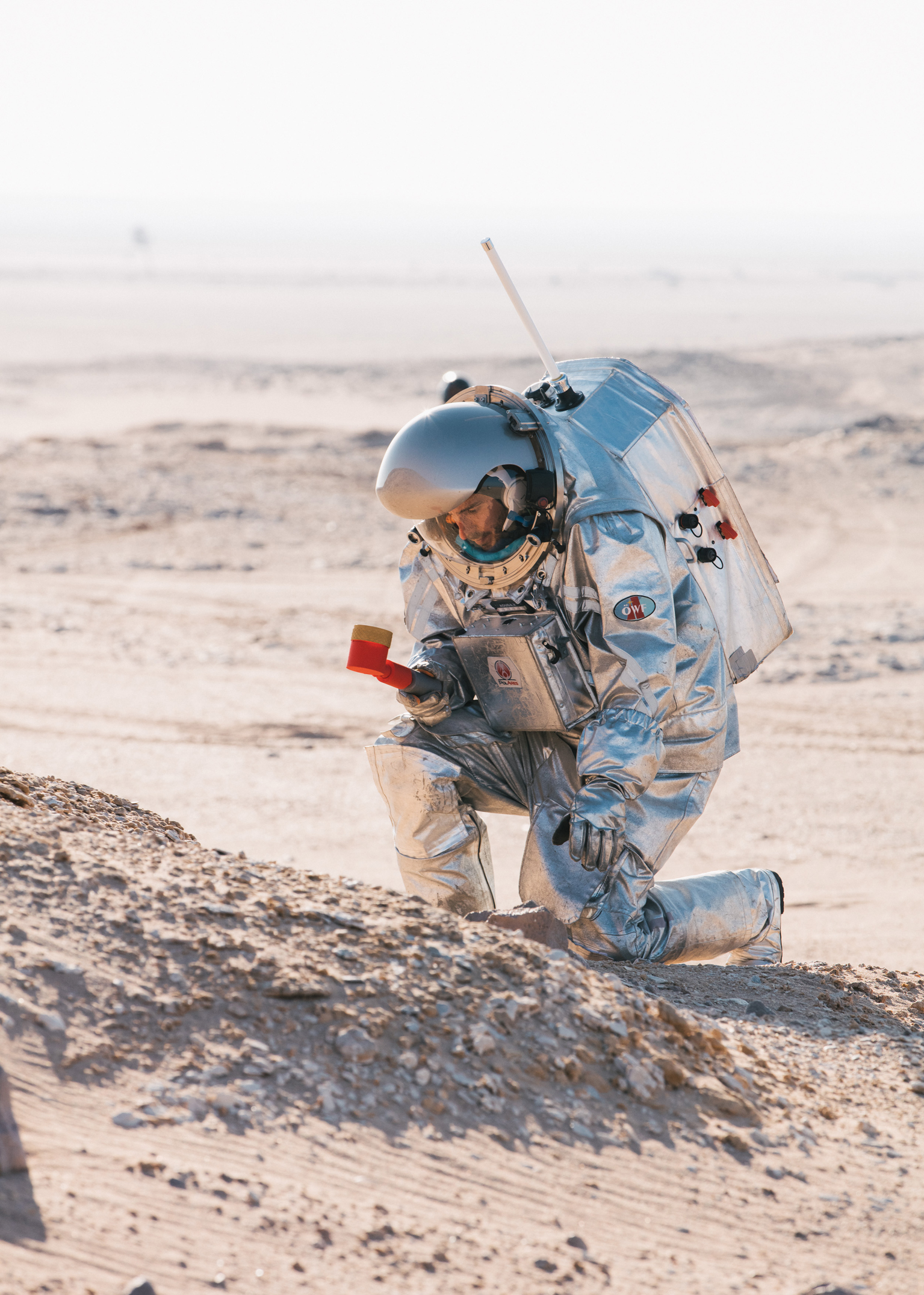 A man in a space suit kneeling takes samples in the red desert sand. He holds a tool in one hand.