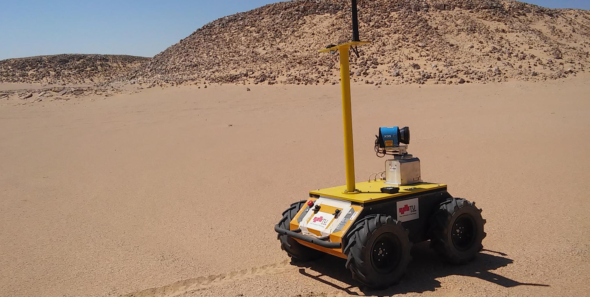 Brauner Wüstensand. Steine im Hintergrund. Vorne steht ein Roboter - er ist gelb, geformt wie eine Kiste und hat eine lange Antenne.