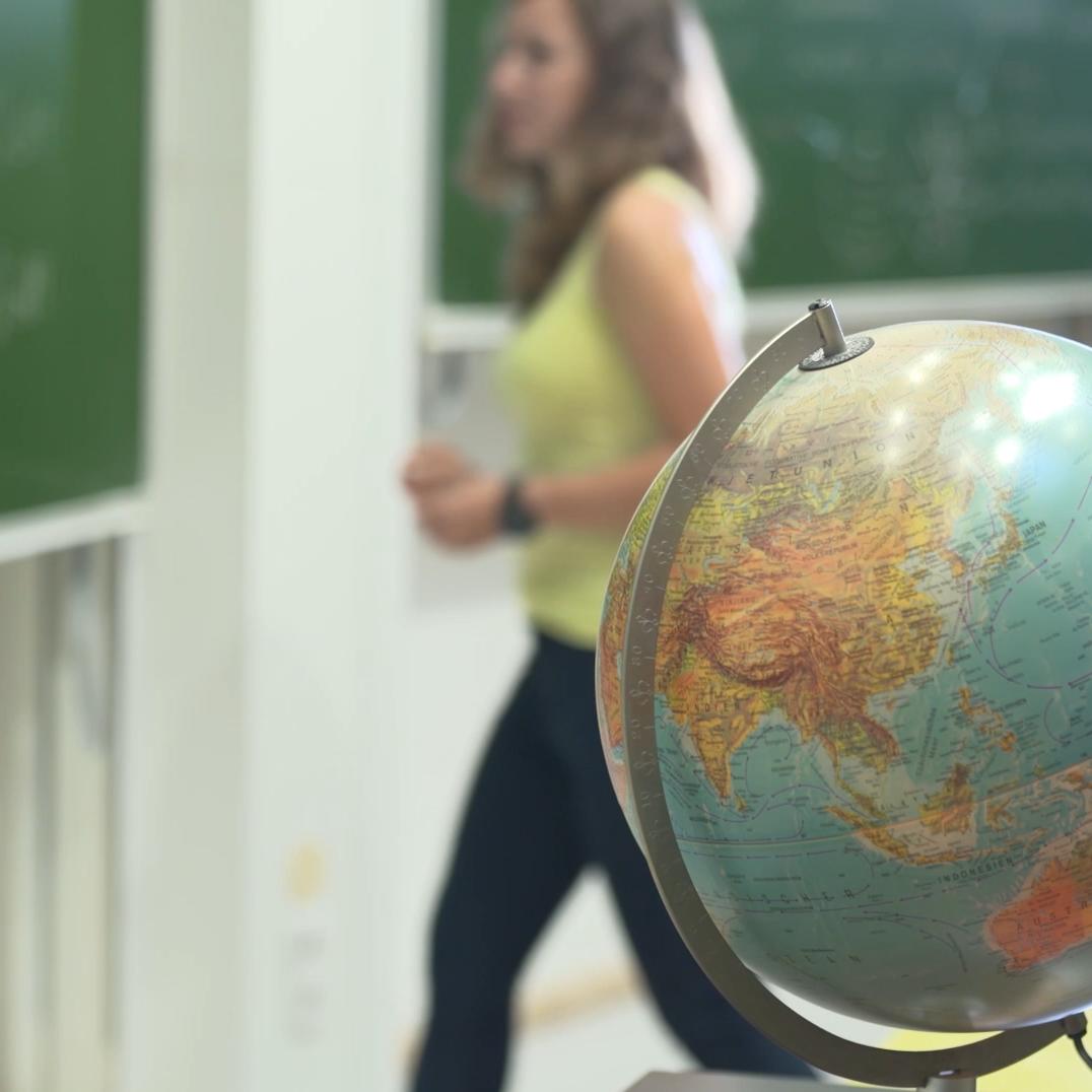 Frau an einer Tafel hinter einem Globus.