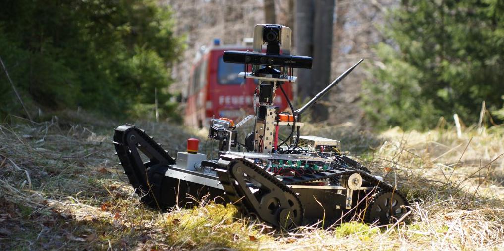 Field Roboter auf Wiese, im Hintergrund ein Feuerwehrfahrzeug.