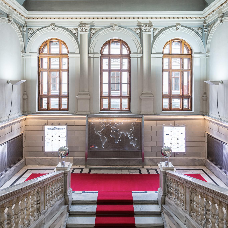 Großzügiger Treppenaufgang mit hohen Fenstern und rotem Teppich.