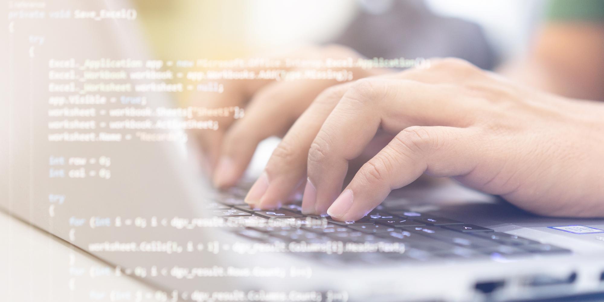Hände auf einer Computertastatur, im Vordergrund stehen mehrere Zeilen einer Programmiersprache.