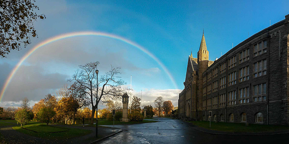 Wunderschönes altes Universitätsgebäude mit einem fantastischen Regenbogen, der das herbstliche Parkgelände am Campus der Norwegian University of Science and Technology (NTNU) überspannt.